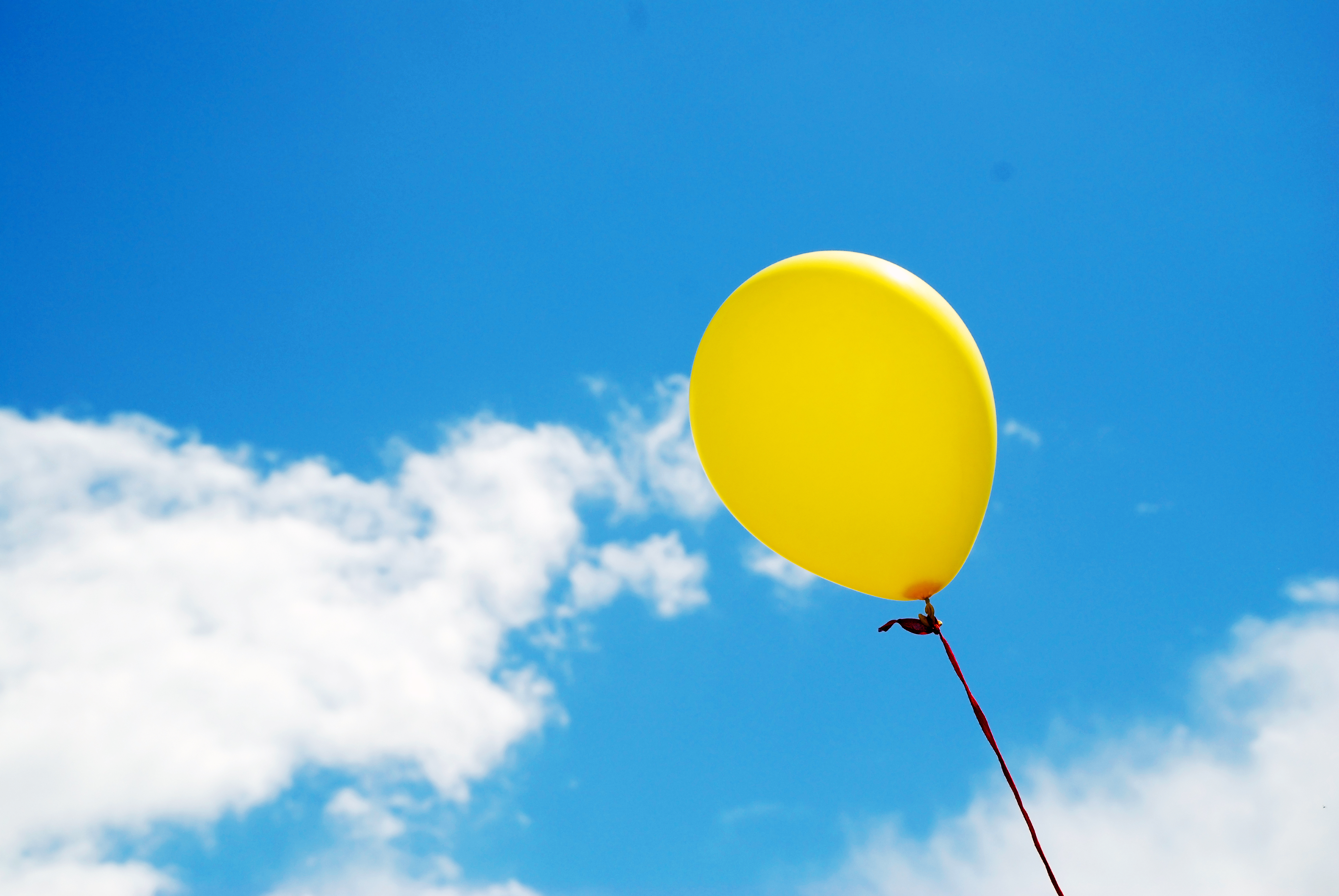 Yellow balloon in sky